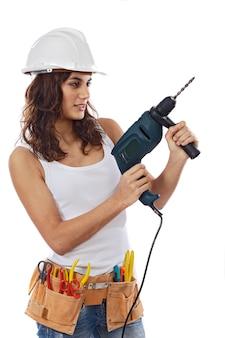 Młoda dziewczyna z narzędziami dla budować na białym tle