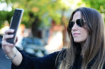 Młoda kobieta bierze selfie z jej smartphone.