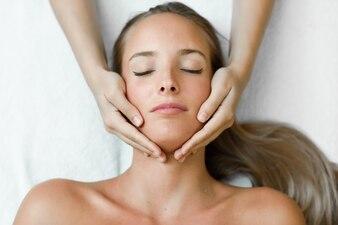 Młoda kobieta otrzymania masaż głowy w centrum spa.