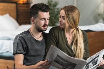 Młoda kobieta patrzeje mężczyzna czytelniczą gazetę w domu