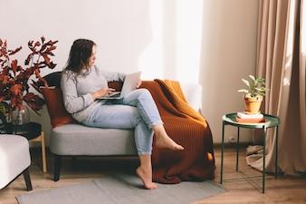 Młoda kobieta pracuje na notatniku. Dziewczyna leży na kanapie.