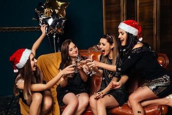 Młode szczęśliwe dziewczyny piją szampana przy przyjęciem gwiazdkowym