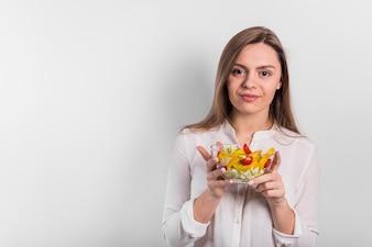 Młodej kobiety pozycja z jarzynową sałatką w pucharze