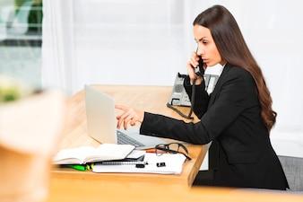 Młody bizneswoman opowiada na telefonicznym patrzeje laptopie w biurze