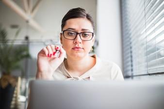 Młody bizneswoman patrzeje laptop