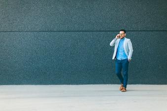 Młody człowiek chodzi i opowiada nad telefonem komórkowym plenerowym