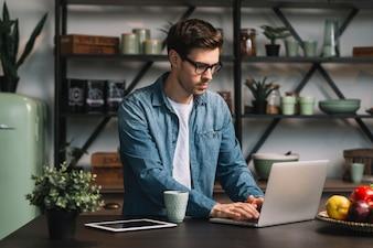 Młody człowiek jest ubranym eyeglasses używa laptop na kuchennym kontuarze