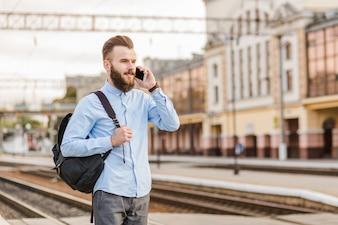 Młody człowiek opowiada na telefonie komórkowym przy stacją kolejową z plecakiem