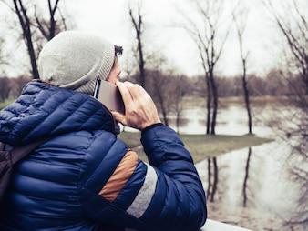 Młody człowiek używa telefon komórkowego w parku