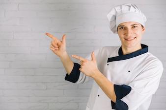 Młody kucharz wskazując palcami gdzieś