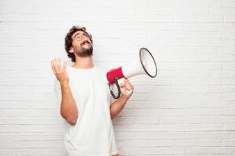 Młody szalony mężczyzna z megafonem przeciw ściana z cegieł.