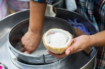 Młyn kokosowy z lodami wygrzebanymi w łupinach orzecha kokosowego