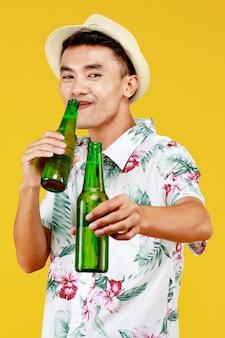 M?oda atrakcyjna azjatyckich cz?owiek w bia?ej koszuli hawajski sobie bia?y kapelusz picie i przytrzymanie dwóch butelek piwa na ?ó?tym tle. koncepcja na wakacje na plaży.