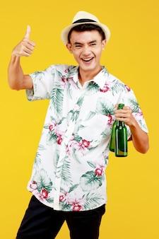 M?oda atrakcyjna azji cz?owiek w bia?ej hawajskiej koszuli na sobie bia?y kapelusz trzyma butelk? piwa i kciuk na ?ó?tym tle. koncepcja na wakacje na plaży.