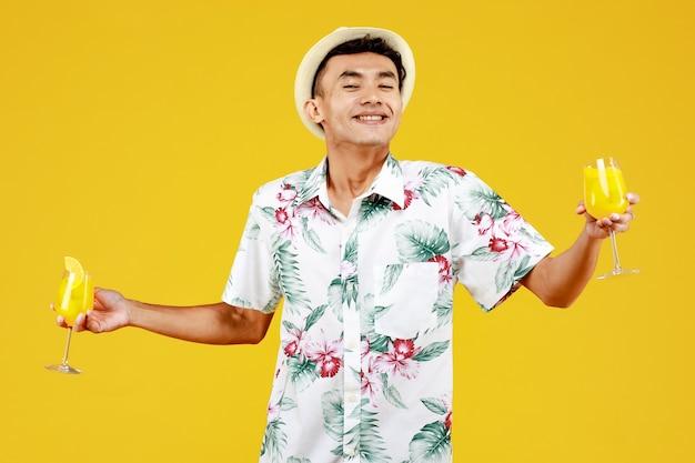 M?oda atrakcyjna azji cz?owiek w bia?ej hawajskiej koszuli trzyma dwie szklanki soku pomara?czowego na ?ó?tym tle. koncepcja na wakacje na plaży.