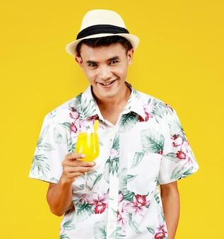 M?oda atrakcyjna azji cz?owiek w bia?ej koszuli hawajski trzyma szklank? soku pomara?czowego na ?ó?tym tle. koncepcja na wakacje na plaży.