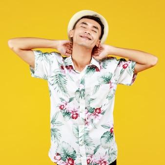 M?oda atrakcyjna azji cz?owiek w bia?ej koszuli hawajskiej sobie bia?y kapelusz relaks na ?ó?tym tle. koncepcja na wakacje na plaży.