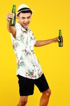 M?oda atrakcyjna azji cz?owiek w bia?ej koszuli hawajskiej sobie bia?y kapelusz trzyma dwie butelki piwa i okrzyki przed ?ó?tym tle. koncepcja na wakacje na plaży.