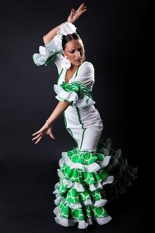 M? oda flamenco tancerka w pi? knej sukni na czarnym tle.