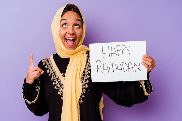 M? oda kobieta maroka posiadaj? ca szcz ?? liwy afisz ramadan wyizolowanych na fioletowym tle m? oda kobieta maroka posiadaj? ca szcz ?? liwy afisz ramadan odizolowane na fioletowym tle wskazuj? cw gór? z otwartymi ustami.