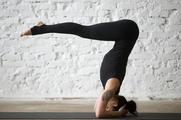 M? oda kobieta yogi atrakcyjne kobiety w stojaku headstand, bia? e loft backgr