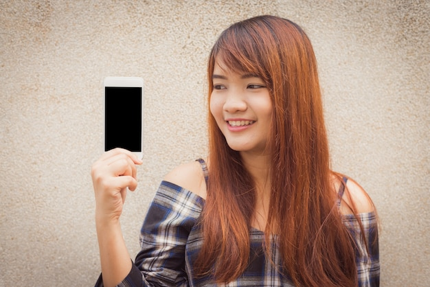 M? oda kobieta z br? zowe w? osy u? miechni? te pokazano pusty ekran smartfona stoj? cy na? cian? obrazy stylu efektów klasycznych.