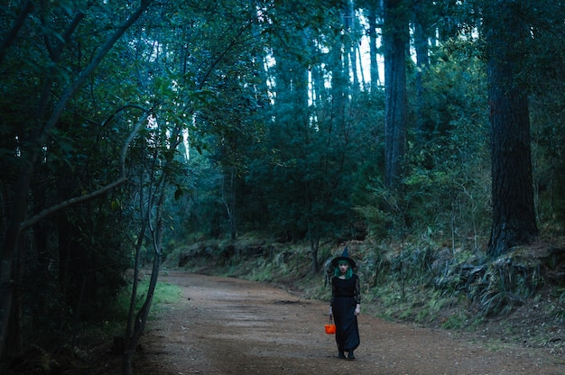 M? oda kobieta z koszem w creepy lasu