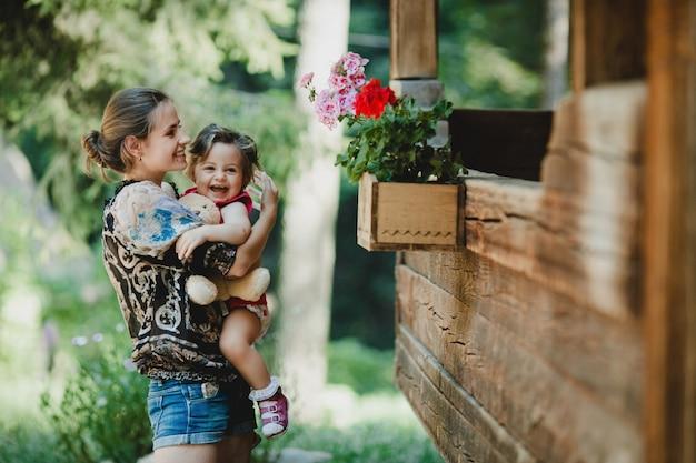 M? oda matka trzyma radosne ma? e dziecko stoj? cej z ni? przed stary drewniany dom