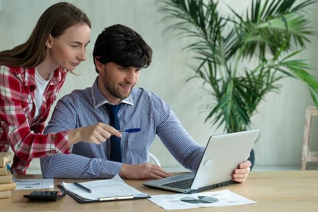 M? oda para pracuj? cych razem w biurze m? oda kobieta, wskazuj? c na laptopa z u? miechem i omawiania co? ze swoim współpracownikiem
