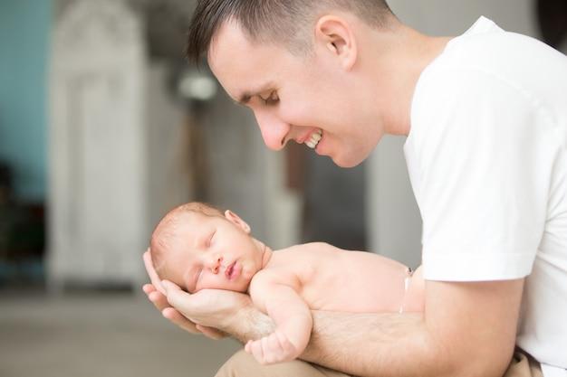 M? oda u? miechni? ta m ?? czyzna trzyma noworodków w jego dłoniach