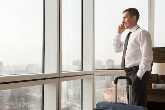 M? ody biznesmen podejmowania rozmowy w pokoju hotelowym