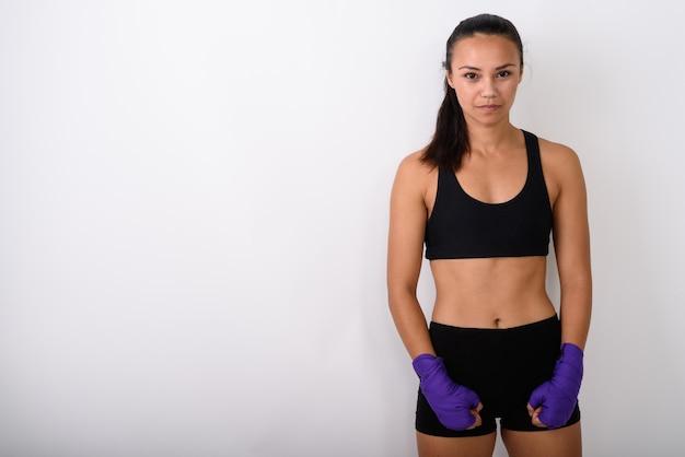M? odych azjatyckich kobieta wojownik stoj? ca z opakowaniami bokserskimi przeciwko spacji
