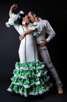 M? odych flamenco tancerzy w pi? knej sukni na czarnym tle.