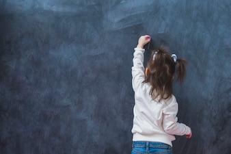 Mała dziewczynka robi linii z kredą