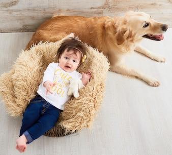 Małe dziecko leży w koszyku obok psa