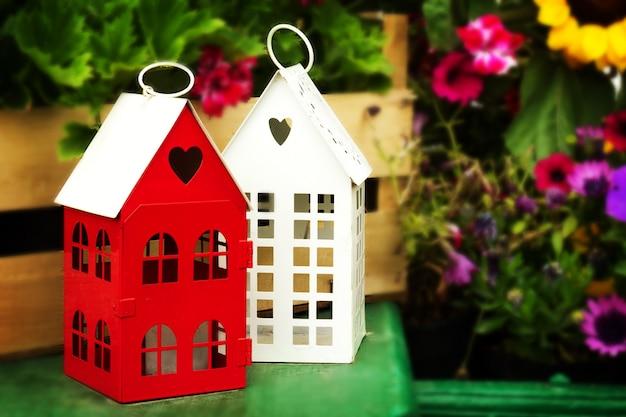 Ma? e cute garden domy z kszta? cie serca windows na zielonym drewnianym stole w ogrodzie z pi? knymi kwiatami na tle.