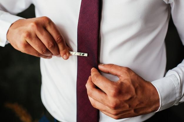 Ma na sobie białą koszulę z czerwonym krawatem. przystojny facet z zadbanymi rękami poprawia krawat z bliska.