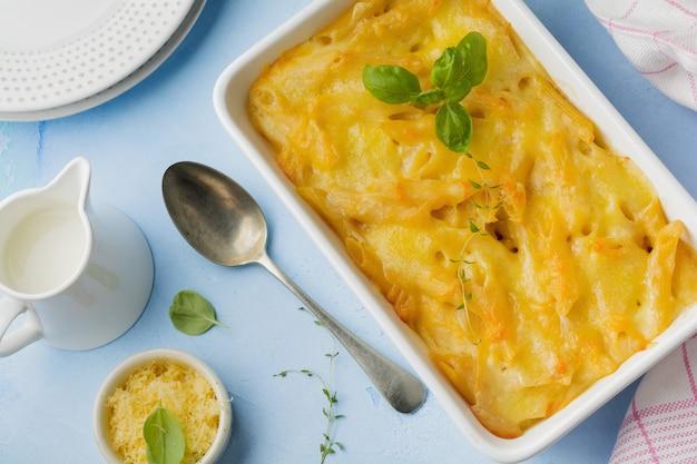 Mac i ser. zapiekanka z makaronu, sera i sosu beszamelowego w formie ceramicznej na jasnym betonie lub kamieniu.