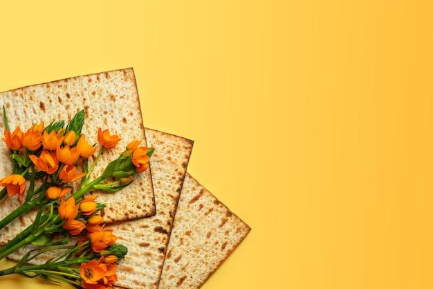 Maca i kwiaty na żółtym tle, widok z góry. koncepcja obchodów paschy (pesach) seder pesah (żydowskie święto paschy). widok z góry