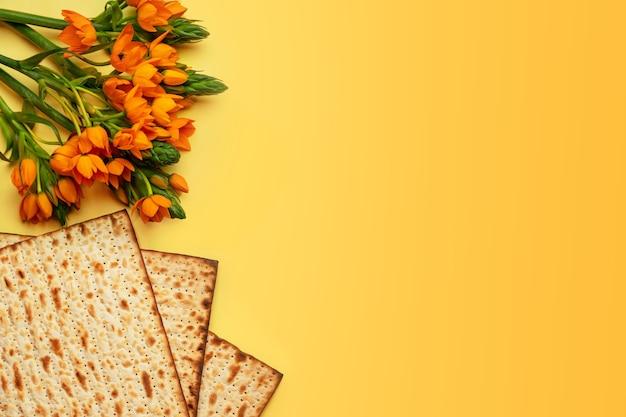 Maca i kwiaty na żółtym tle, widok z góry. koncepcja obchodów paschy (pesach) seder pesah (żydowskie święto paschy).