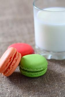 Macaron trzy kawałki czerwony, zielony, pomarańczowy i szklanka z mlekiem na płótnie obrus.