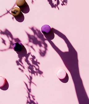 Macarons i kobiecy cień dłoni na różowej powierzchni