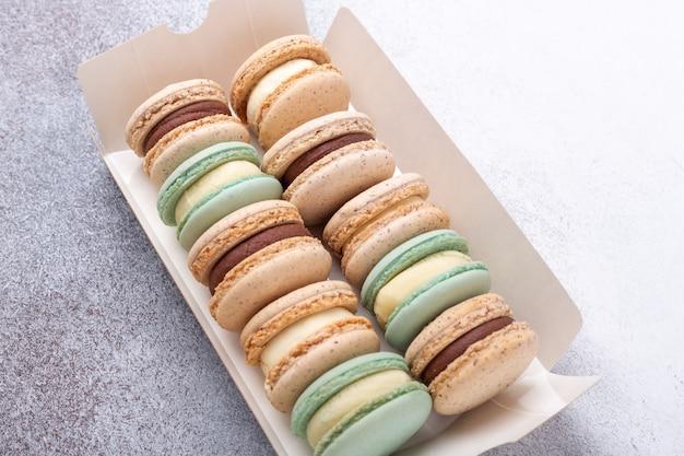 Macarons w polu na kamiennym tle. pyszne francuskie makaroniki. miejsce kopiowania, widok z góry - obraz