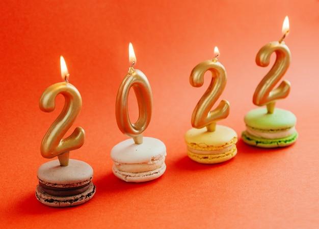 Macarons z płonącymi świecami 2022 na czerwonym tle. nowy rok.