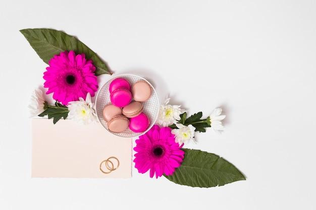 Macaroons na talerzu między kwiatami, ulistnieniem, papierem i pierścionkami ,.