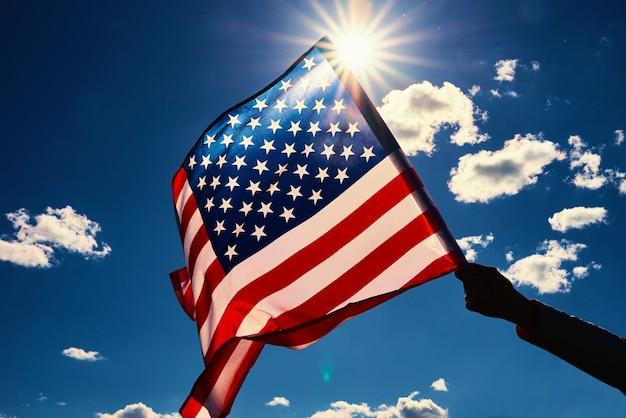 Macha amerykańską flagą na zewnątrz ręka trzyma flagę narodową usa na tle błękitnego pochmurnego nieba