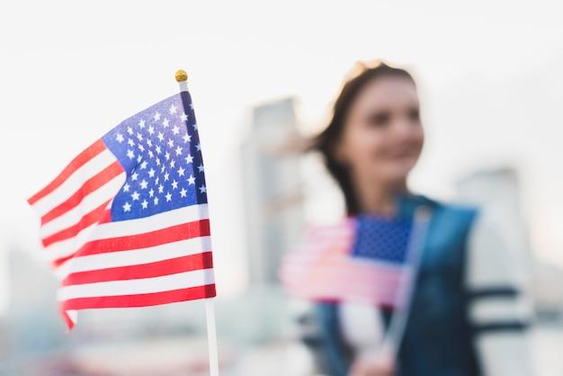 Macha amerykańską flagą w dzień niepodległości