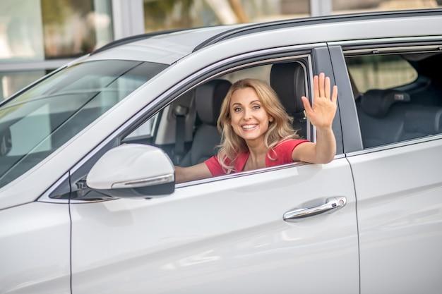 Macha ręką. ładna kobieta siedzi w samochodzie, uśmiecha się i macha ręką