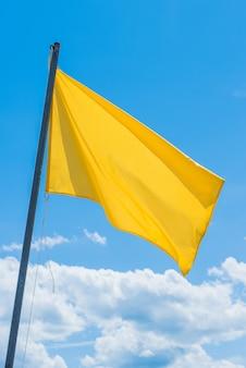 Macha zieloną flagą wskazującą na potencjalnie wysoki poziom fal na plaży