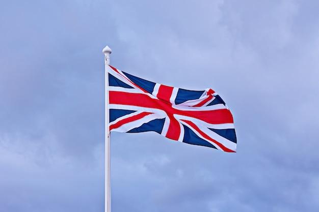 Machać flagą wielkiej brytanii na niebieskim tle pochmurnego nieba.